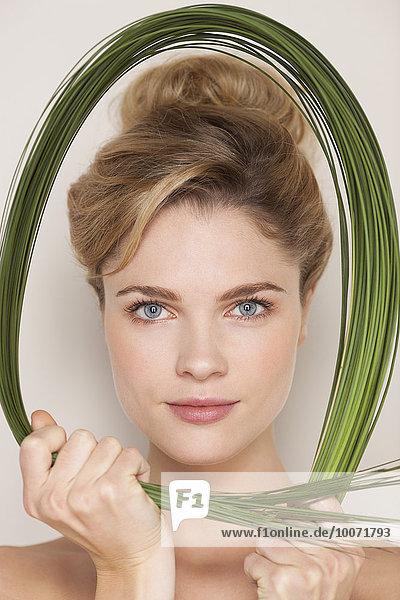 Portrait of a beautiful woman holding wheatgrass