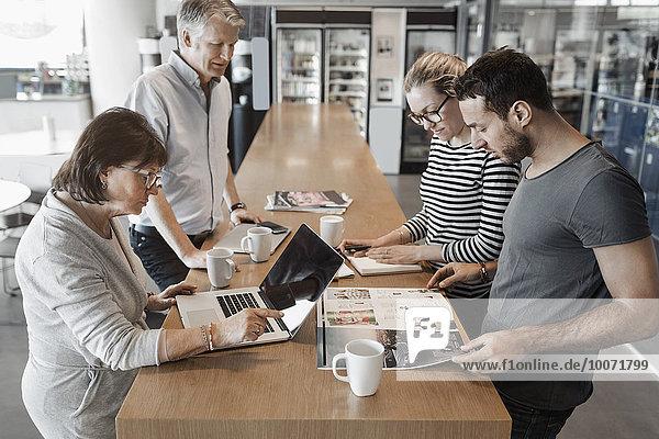 Multiethnische Geschäftsleute  die am Schalter im Bürocafé arbeiten
