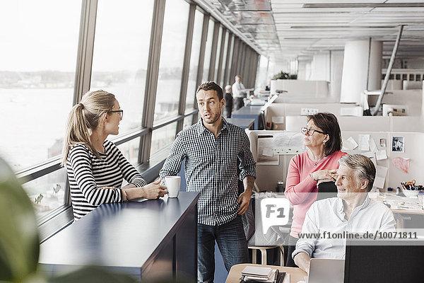 Geschäftsleute diskutieren in der Kabine im Büro