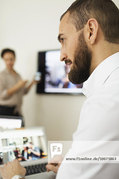 Young businessman looking away in office