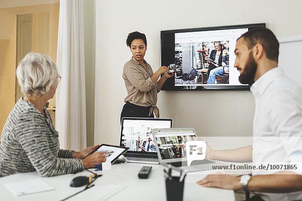 Seitenansicht der Geschäftsfrau bei der Präsentation vor Kollegen im Büro