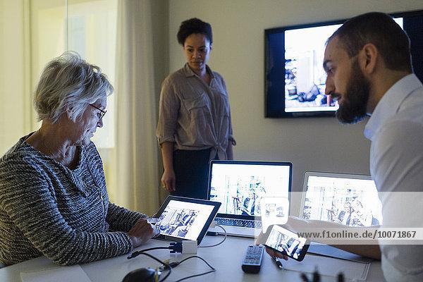 Geschäftsleute  die Technologien während des Meetings nutzen