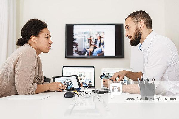 Seitenansicht von Geschäftsleuten,  die Technologien am Tisch nutzen