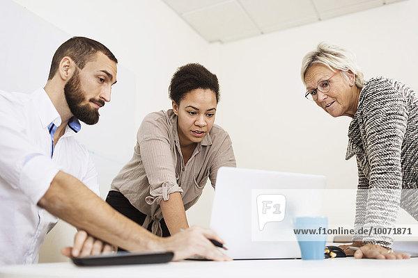 Geschäftsleute mit Laptop am Tisch im Büro
