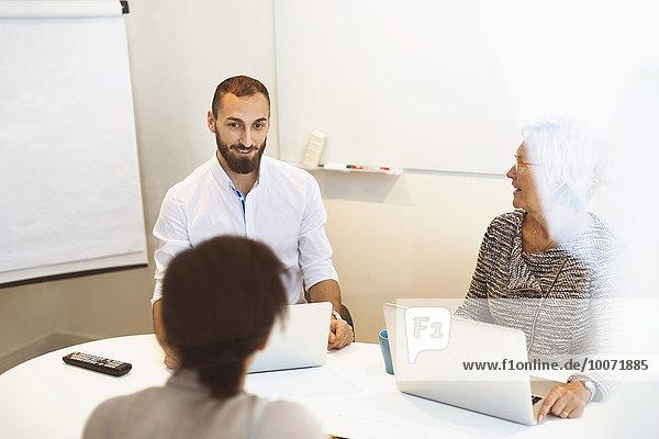Geschäftsleute mit Laptops am Konferenztisch im Büro