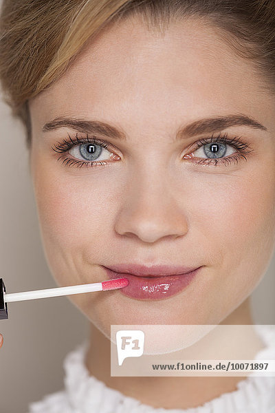 Porträt einer schönen Frau  die Lipgloss aufträgt