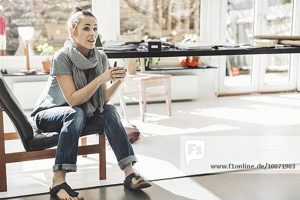 Architektin schaut weg  während sie auf einem Stuhl im Home-Office sitzt.