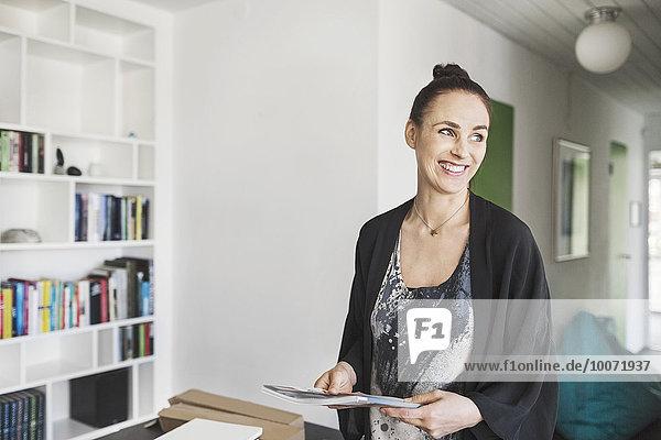 Glückliche Architektin mit Buch im Home-Office