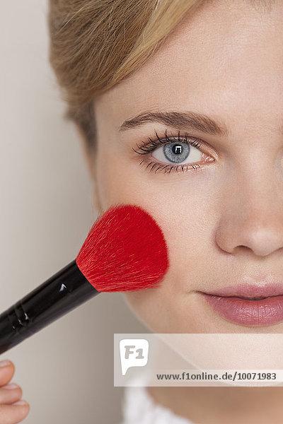 Porträt einer Frau mit Schminkpinsel im Gesicht