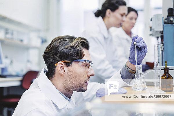 Männlicher Wissenschaftler untersucht Probe im Labor mit weiblichen Kollegen im Hintergrund