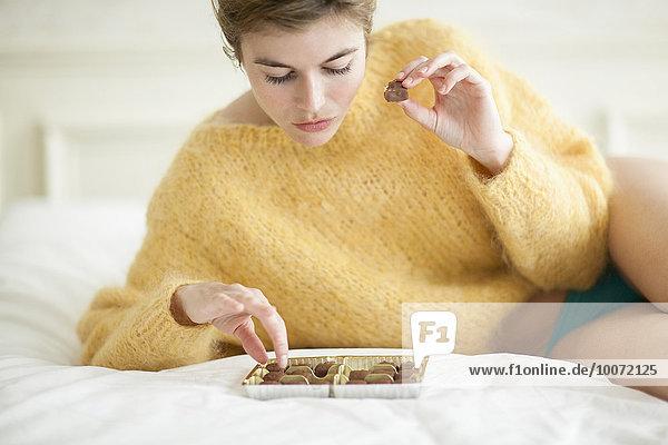 Frau isst Schokolade auf dem Bett Frau isst Schokolade auf dem Bett