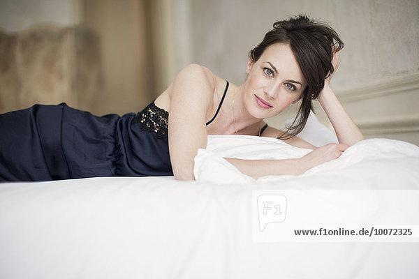 Porträt einer schönen Frau auf dem Bett liegend