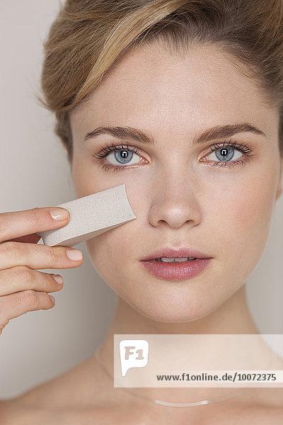Beautiful woman using sponge on face