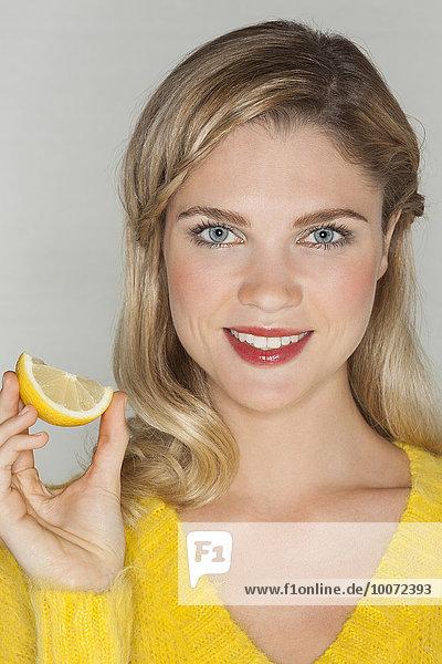 Porträt einer schönen Frau mit einem Stück Orange und lächelndem Gesicht