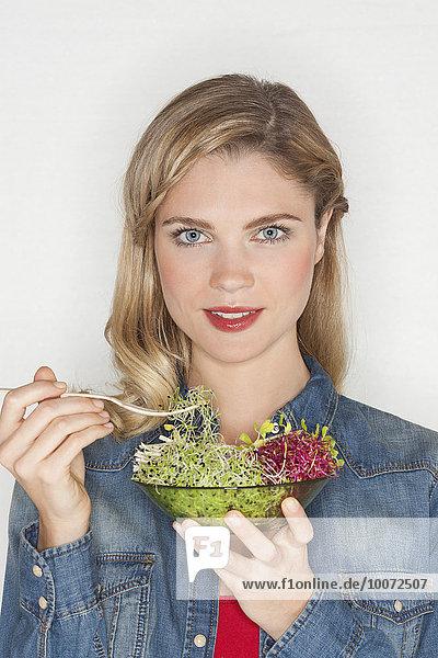 Porträt einer schönen Frau  die Bohnensprossen isst