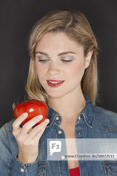 Nahaufnahme einer Frau  die eine Tomate ansieht und lächelt