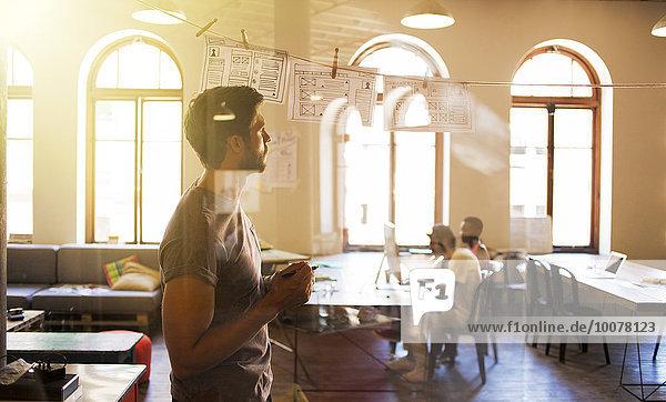 Kreatives Geschäftsmann-Brainstorming mit hängenden Diagrammen