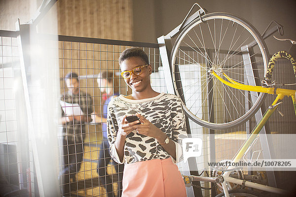 Lächelnde Geschäftsfrau beim SMSen auf dem Handy neben dem Fahrrad
