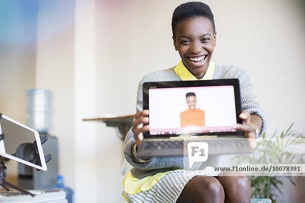 Portrait lächelnde Geschäftsfrau mit Selbstfoto am Laptop