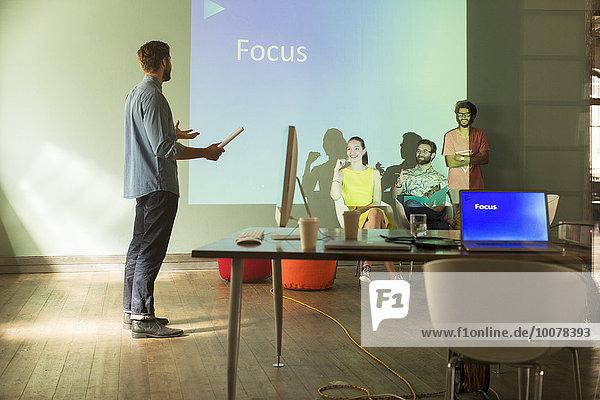 Geschäftsleute bei der Vorbereitung einer audiovisuellen Präsentation auf Focus