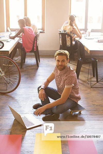 Portrait kreativer Geschäftsmann bei der Arbeit am Laptop auf dem Boden