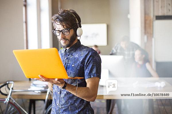 Lässiger Geschäftsmann mit Kopfhörer und Laptop im Büro