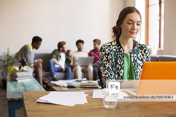 Kreative Geschäftsfrau am Laptop mit Papierkram im Büro