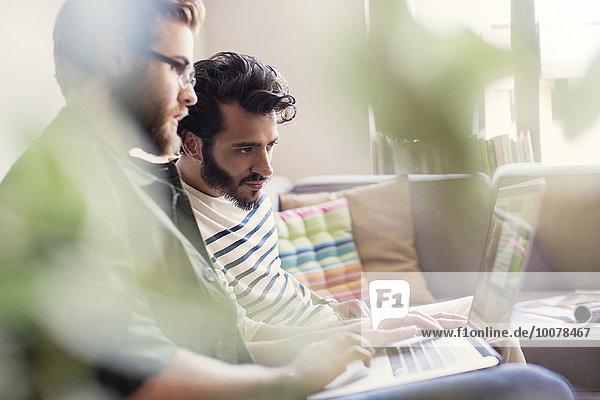Casual Geschäftsleute arbeiten am Laptop auf Sofa im Büro