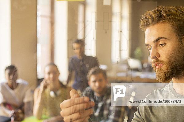 Gelegentlich Geschäftsmann erklärt Diagramm auf Glas in der Sitzung