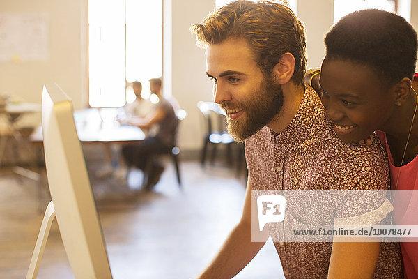 Lächelnde Geschäftsleute  die sich den Computer im Büro teilen.