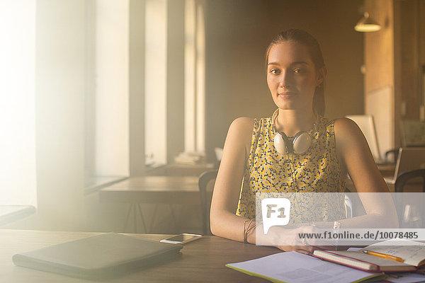 Porträt einer lässigen Geschäftsfrau mit Kopfhörer im Büro