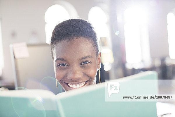 Portrait lächelnde Geschäftsfrau hinter Buch im Büro
