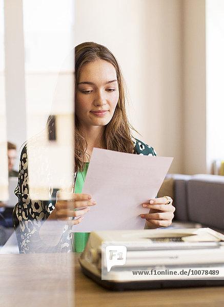 Kreative Geschäftsfrau bei der Überprüfung der Schreibmaschine im Büro