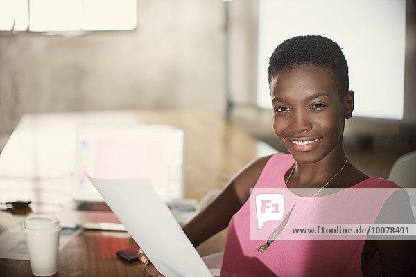 Portrait lächelnde Geschäftsfrau mit Papierkram im Büro