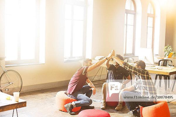 Kreative Geschäftsleute im Kreis im sonnigen Büro