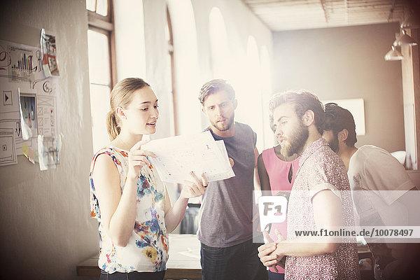 Gelegentliche Geschäftsleute  die den Papierkram im Büro besprechen