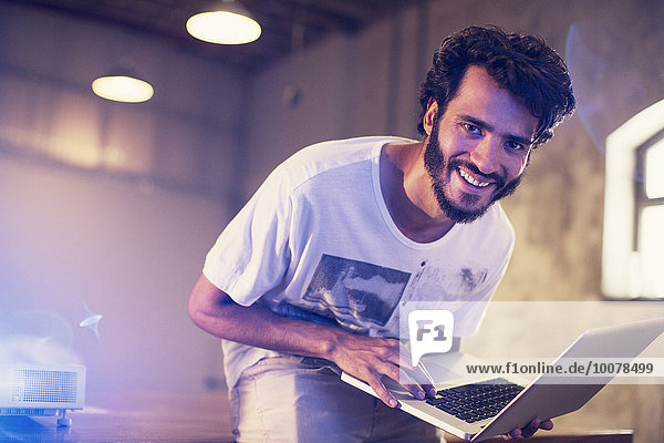 Portrait begeisterter Gelegenheitsunternehmer mit Laptop im Büro