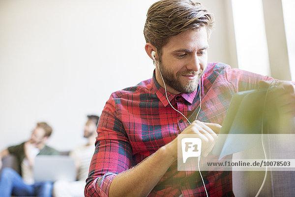 Lässiger Geschäftsmann mit Kopfhörer und digitalem Tablett im Büro