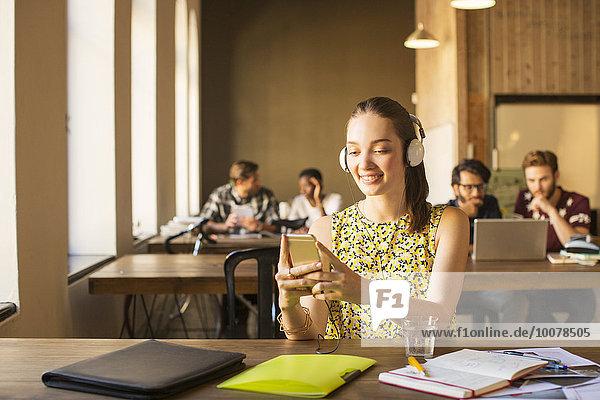 Lässige Geschäftsfrau mit Kopfhörer über Handy im Büro