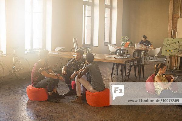 Lässige Geschäftsleute treffen sich im Kreis im sonnigen Büro