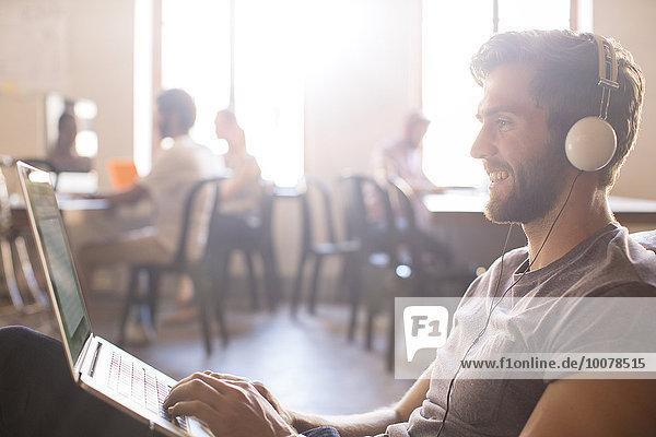 Lässiger Geschäftsmann mit Kopfhörer und Arbeit am Laptop im Büro