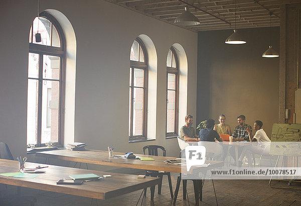 Lässige Geschäftsleute treffen sich am Tisch im Büro