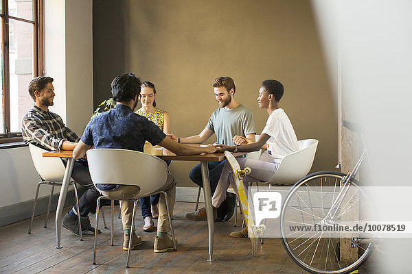 Kreative Geschäftsleute  die bei der Besprechung am Tisch Händchen halten