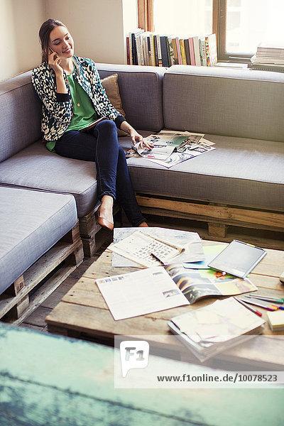Kreative Geschäftsfrau beim Korrekturlesen und Telefonieren auf dem Bürosofa