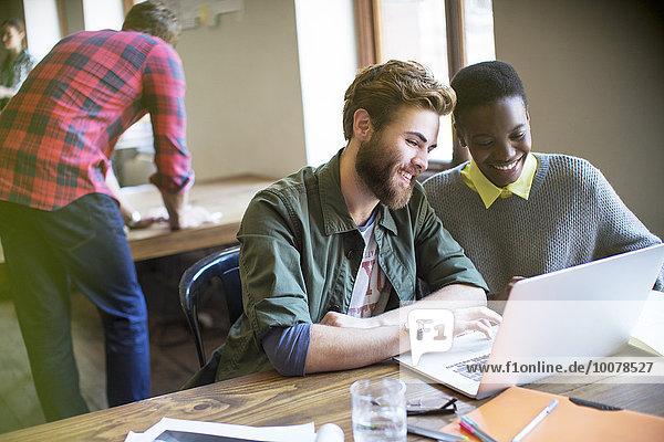 Lächelnde Geschäftsleute  die am Laptop im Büro arbeiten