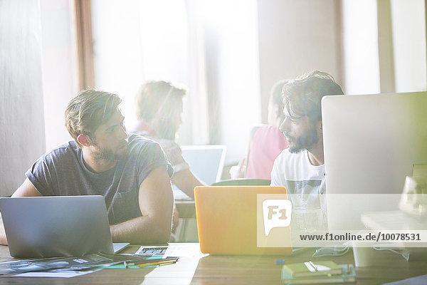 Kreative Geschäftsleute  die an Laptops arbeiten und sich im Büro unterhalten.