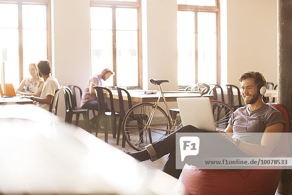Lächelnder Geschäftsmann mit Kopfhörer und Arbeit am Laptop am Bohnensackstuhl im Büro