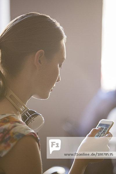 Nahaufnahme Frau mit Kopfhörer über Handy