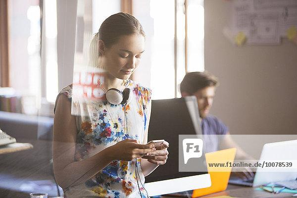 Lässige Geschäftsfrau mit Kopfhörer SMS auf dem Handy im Büro