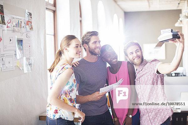 Kreative Geschäftsleute nehmen Selfie mit Sofortbildkamera im Büro